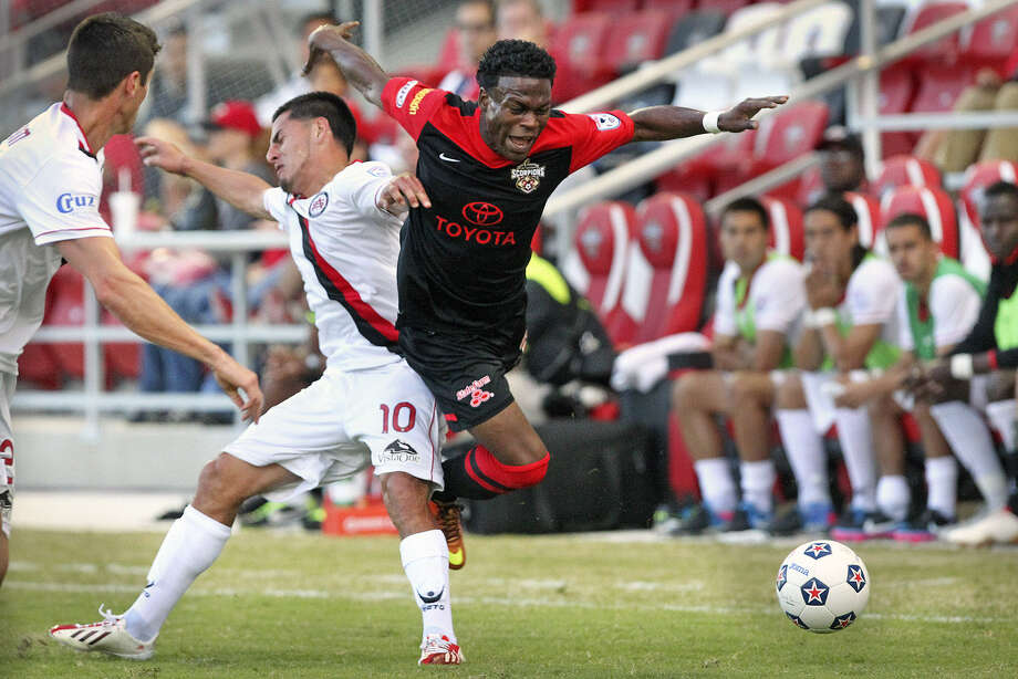 The Scorpions' Walter Ramirez (right) trips over Atlanta's Danny Barrera as he tries to run upfield during Saturday's match at Toyota Field. Photo: Tom Reel / San Antonio Express-News