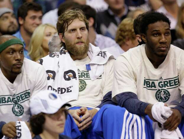Dallas Mavericks power forward Dirk Nowitzki, center, of Germany sits on the bench with teammates Jae Crowder, right, and Anthony Morrow during the basketball game against the Phoenix Suns Wednesday, April 10, 2013, in Dallas.  The Suns pushed the Mavericks to the brink of playoff elimination for the first time since 2000 with a 102-91 victory. (AP Photo/LM Otero) Photo: Associated Press / AP
