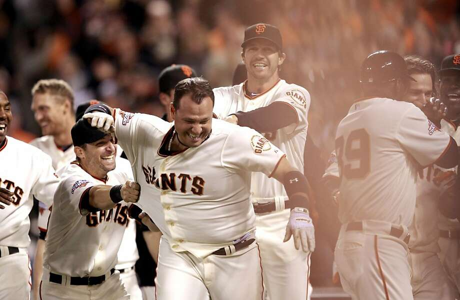 Guillermo Quiroz is greeted by Marco Scutaro (left), Barry Zito and the Giants after his homer. Photo: Michael Macor, The Chronicle