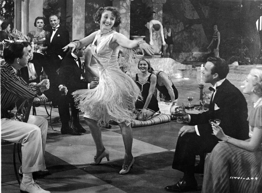 "An unidentified woman wearing a 'flapper'- style skirt dances at a party, as actor Shelley Winters as Myrtle Wilson (center) watches in the background in a still from the film, ""The Great Gatsby,"" directed by Elliott Nugent, 1949."