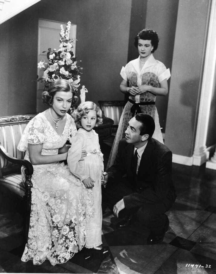 "Actors Betty Field  as Daisy Buchanan and Macdonald Carey  as Nick Carraway speak to a young girl as Ruth Hussey, Jordan Baker, looks on in a still from the film, ""The Great Gatsby,"" 1949."