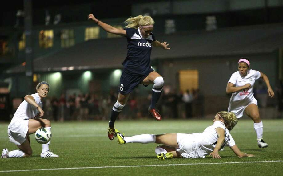 Seattle Reign FC player Kaylyn Kyle leaps over an FC Kansas City player during the Reign's first home match on May 4, 2013 at Starfire Sports in Tukwila. Reign FC is Seattle's new women's pro soccer team. They lost to Kansas 0-1. Photo: JOSHUA TRUJILLO, SEATTLEPI.COM / SEATTLEPI.COM
