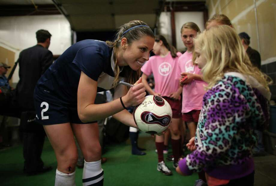 Seattle Reign FC player Emily Zurrer autographs a ball for a young fan during the Reign's first home match on May 4, 2013 at Starfire Sports in Tukwila. Reign FC is Seattle's new women's pro soccer team. They lost to Kansas 0-1. Photo: JOSHUA TRUJILLO, SEATTLEPI.COM / SEATTLEPI.COM