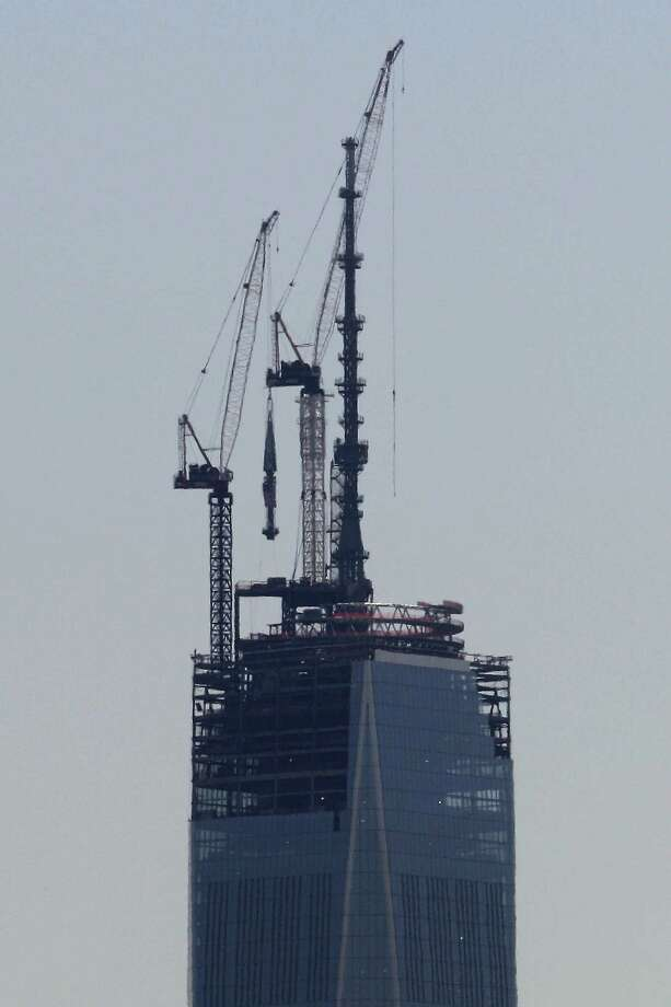 A 408-foot spire, center, is lifted toward the top of the construction of One World Trade Center seen from the Heights neighborhood of Jersey City, N.J., Thursday, May 2, 2013. The spire, which will put the building at 1,776 feet tall, will be placed on the structure at a later day. Photo: AP