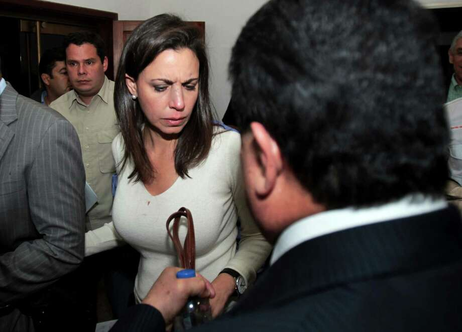 Opposition lawmaker Maria Corina Machado is escorted by party members as she arrives to her political party's headquarters before a press conference in Caracas, Venezuela, Tuesday, April 30, 2013.  Members of Venezuela's National Assembly say post-election tensions set off a brawl Tuesday night between lawmakers that left opposition legislator Julio Borges badly bruised and bleeding, after he and other opposition lawmakers tried to protest a proposal barring them from legislative activities.  The opposition has refused to accept President Nicolas Maduro's narrow April 14 victory, prompting the pro-government side to try to bar them from the assembly. Tuesday's fight was the second in which opposition legislators said the other side attacked them. Photo: AP