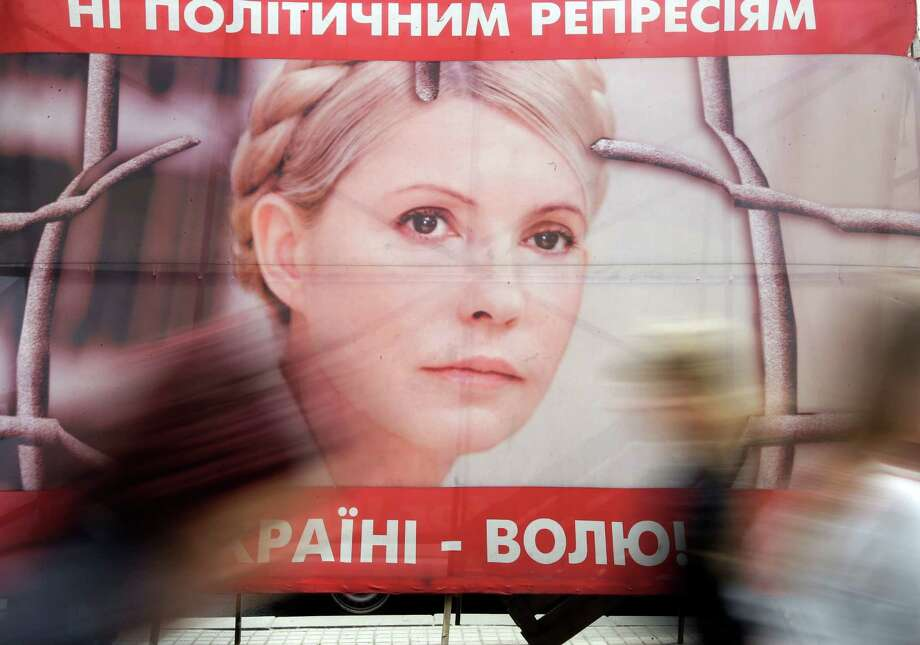 "People pass by a poster of Ukraine's imprisoned former Prime Minister Yulia Tymoshenko at a tent camp of her supporters in central Kiev, Ukraine, Tuesday, April 30, 2013. Ukraine's jailing of former Prime Minister Yulia Tymoshenko was a politically motivated violation of her rights, Europe's human rights court ruled Tuesday. The poster with Tymosneko reads ""Freedom to Ukraine"", ""No political repression"". Photo: AP"
