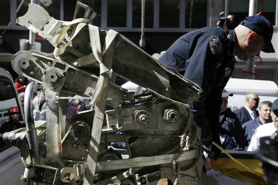 Officials load a plane part that was discovered wedged between an apartment building and a mosque into a truck in New York, Wednesday, May 1, 2013. Authorities believe the plane part is from one of the two hijacked airliners that brought down the trade center on Sept. 11, 2001. Photo: AP