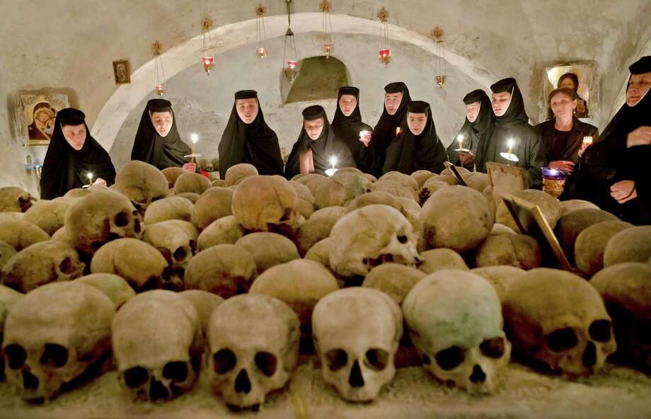 Romanian orthodox nuns sing in the ossuary at the Pasarea monastery, outside Bucharest, Romania, Sunday, May 5, during the Easter Religious service. The ossuary, containing mostly remains of the nuns that lived at the monastery is briefly opened on Easter night. Photo: AP