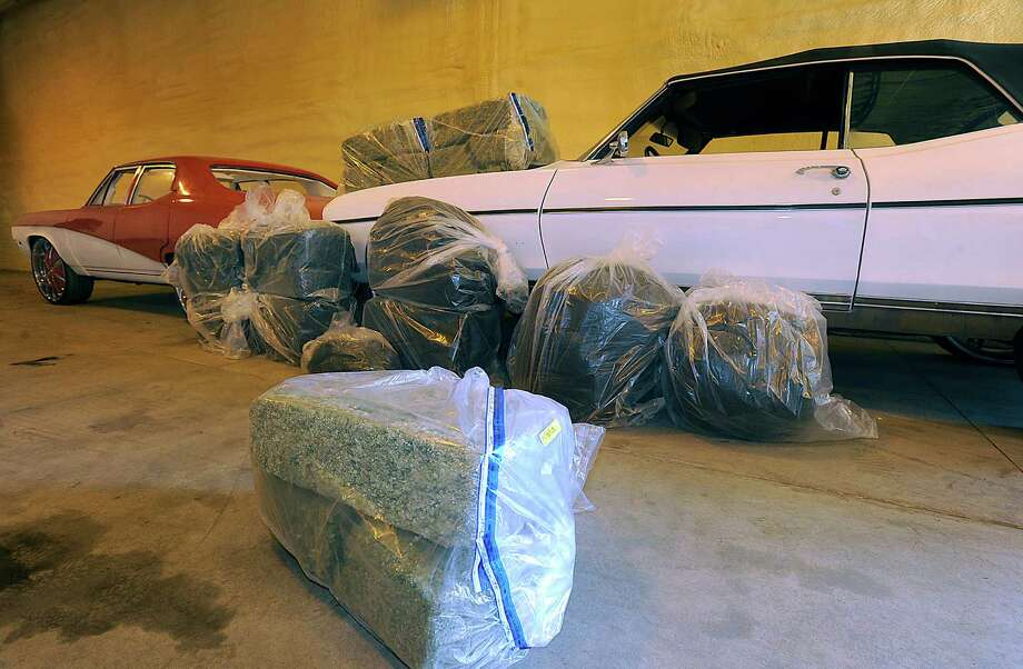 Drugs and vehicles seized are on display at the Erie Regional Office Attorney General's Bureau of Narcotics Investigation and Drug Control, in Millcreek Township, Pa. on Tuesday, April 30, 2013. Agents with the state Attorney General's Bureau of Narcotics Investigation and Drug Control seized $1.3 million worth of marijuana in a recent drug bust and arrested two men.  (AP Photo/Erie Times-News, Jack Hanrahan) Photo: AP