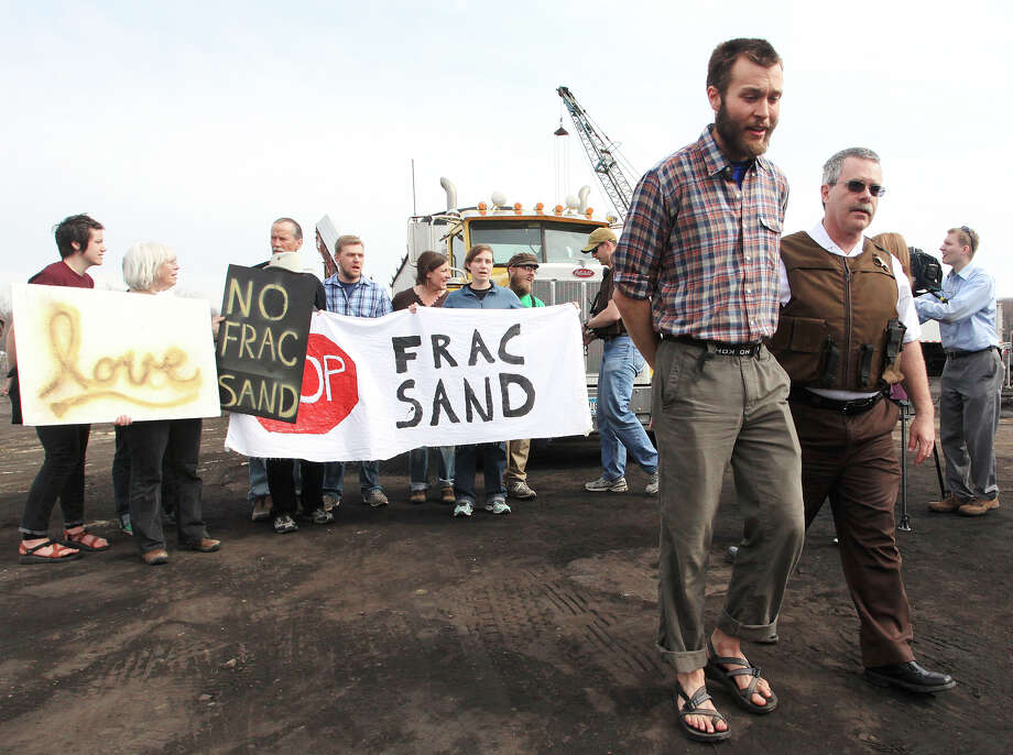 Protester Dan Wilson of Winona, Minn., is escorted away by a Winona County sheriff's deputy during a frac sand protest Monday, April 29, 2013 at Winona's commercial dock on Riverview Drive. At least 40 people were arrested for trespassing and other minor offenses during the protest. Photo: AP