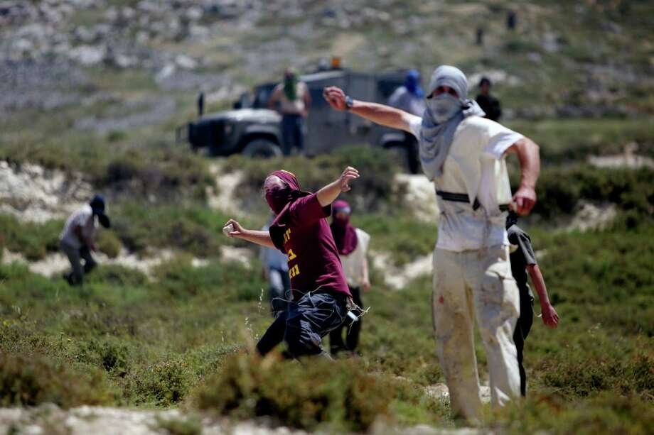 Jewish settlers throws rocks towards Palestinians, not pictured, during clashes near the Jewish settlement of Yitzhar, near Nablus, Tuesday, April 30, 2013. In the West Bank, a Palestinian man fatally stabbed an Israeli waiting at a bus stop and fired on police before he was detained by Israeli security forces, officials said. The Israeli military said that following the stabbing settlers began rioting, hurling rocks at Palestinian vehicles and setting fire to nearby fields. It said two rioters were arrested. Photo: AP