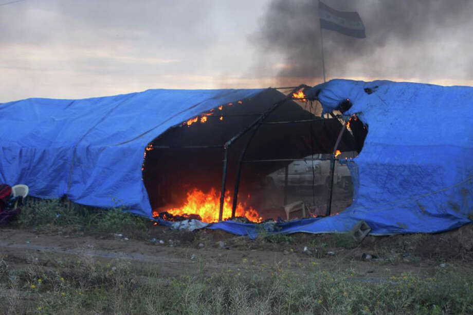 This image released by Human Rights Watch on Saturday, May 4, 2013 shows a tent burning at a Sunni protest camp following a raid by Iraqi security forces that killed scores in Hawija, Iraq on April 23. Human Rights Watch on Saturday urged Iraqi authorities to give a government committee charged with probing a deadly raid by security forces on a protest camp last week greater financial and political backing to investigate who is responsible for what it described as an apparently unlawful use of lethal force. Photo: AP