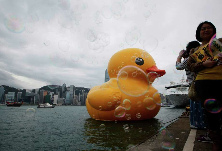 Visitors take picture of a giant Rubber Duck created by Dutch artist Florentijn Hofman in Hong Kong Thursday, May 2, 2013. Since 2007 the 16.5-meter (54-feet)-tall Rubber Duck has traveled to various cites including Osaka, Sydney, Sao Paulo and Amsterdam. Photo: AP