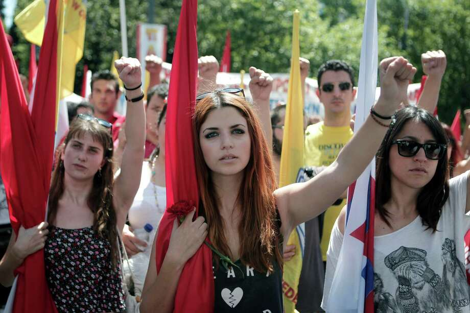 Members of pro-communist union PAME raise their fists during a protest in Athens, on Wednesday, May 1, 2013. About 8,000 people took part in the subdued demonstrations as austerity-weary unions held a strike for May Day. The country's main labor unions are protesting soaring unemployment, which is the highest in the 27-country European Union, and the austerity measures the conservative-led government is enacting in return for crucial bailout loans. Photo: AP