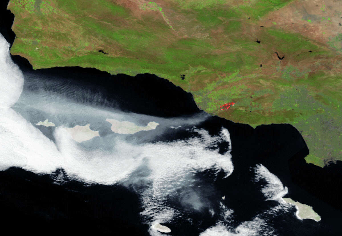 This satellite photo released by NOAA, National Oceanic and Atmospheric Administration, showing a stream of smoke clearly visible moving west over the ocean, as are the heat signatures from the active fires areas. A Southern California wildfire carving a path to the sea grew to more than 15 square miles and crews prepared Friday for another bad day of gusting winds and searing weather.