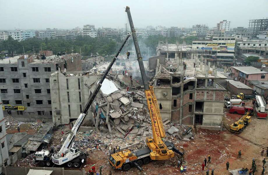 The garment factory building collapsed on Wednesday, is seen from a building nearby as a crane prepares to lift the fallen ceiling, in Savar, near Dhaka, Bangladesh, Monday April 29, 2013. Rescue workers in Bangladesh gave up hopes of finding any more survivors in the remains of a building that collapsed five days ago, and began using heavy machinery on Monday to dislodge the rubble and look for bodies - mostly of workers in garment factories there. At least 381 people were killed when the illegally constructed, 8-story Rana Plaza collapsed in a heap on Wednesday morning along with thousands of workers in the five garment factories in the building. Photo: AP