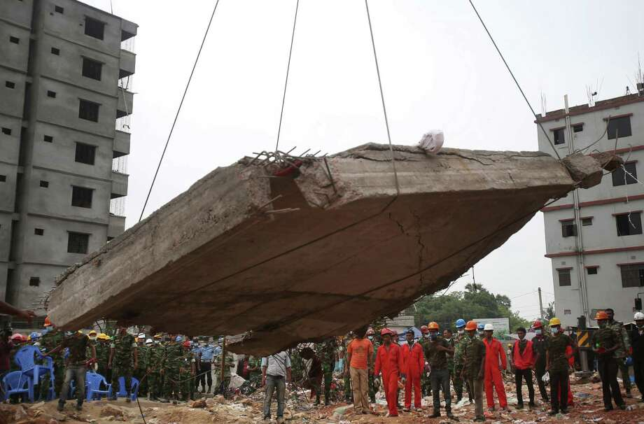 Workers watch as a crane lowers the ceiling of the garment factory building which collapsed in Savar, near Dhaka, Bangladesh on Monday April 29, 2013. Rescue workers in Bangladesh gave up hopes of finding any more survivors in the remains of a building that collapsed five days ago, and began using heavy machinery on Monday to dislodge the rubble and look for bodies - mostly of workers in garment factories there. At least 381 people were killed when the illegally constructed, 8-story Rana Plaza collapsed in a heap on Wednesday morning along with thousands of workers in the five garment factories in the building. Photo: AP