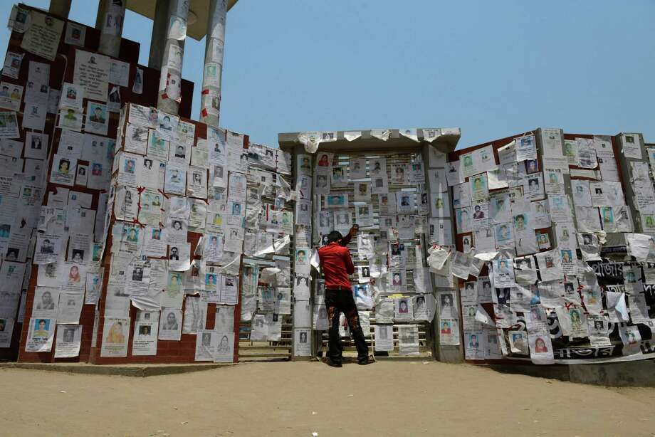Bangladeshi Mohammed Oudud holds a photograph of his wife Parvin and leans on a wall filled with portraits of missing persons near the site of a garments factory that collapsed in Savar near Dhaka, Bangladesh, Friday, May 3, 2013. More than 500 bodies have been recovered from the debris of the building, even as the Bangladeshi government suspended Savar's mayor and arrested an engineer who had called for the building's evacuation last week, but was also accused of helping the owner add three illegal floors to the eight-story structure. Photo: AP