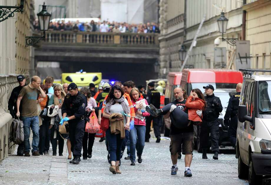 Injured people leave a scene of an explosion in downtown Prague, Czech Republic, Monday, April 29, 2013. Police said a powerful explosion has damaged a building in the center of the Czech capital and they believe some people are buried in the rubble. Photo: AP