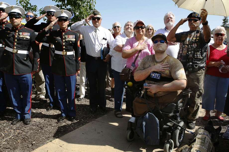Marine Staff Sgt. Jason Ross (right) watches as the flag is raised at Granada High School in Livermore, California, before a baseball game honoring Livermore's wounded warriors on Wednesday, April 24, 2013.  After graduating in 2001, he joined the U.S. Marine Corps later becoming an explosives technician. While in Afghanistan in 2011, he stepped on on an improvised explosive device while patrolling and lost his legs.