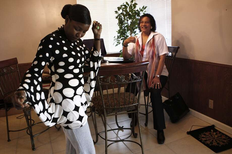 Katrina Mbonisi (left) shows executive employment counselor Lynette Nutting (right) what she wore to yesterday's interview with apparel company White House/Black Market in San Leandro, Calif, on Friday, May 3, 2013.  For the past two years Lynette has been volunteering as vice president of job training as well as doing job fairs and resume critiques at the city employment counseling center in downtown Oakland while trying to make ends meet.