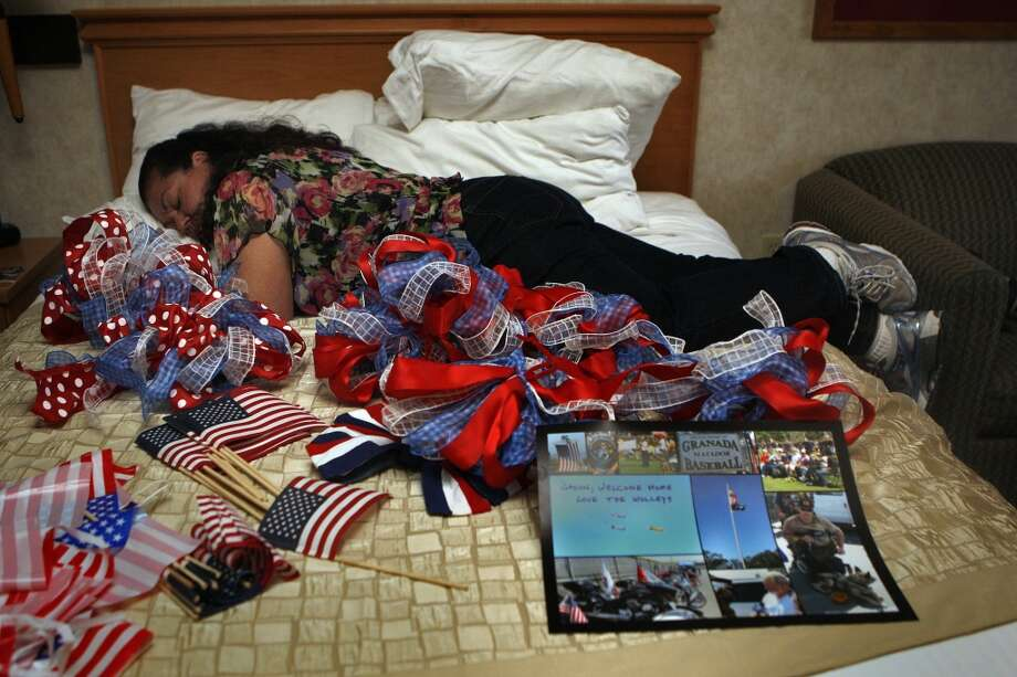 Linda Ross takes a rest after fluffing bows on the bed of her room at Hawthorn hotel in Livermore, California, on Friday, April 26, 2013, for her son's homecoming celebration the next day.  Her son, marine staff Sgt. Jason Ross lost both legs two years ago while on patrol in Afghanistan.  Jason has had 200 surgeries so far and this is his first time visiting his hometown since his injury.