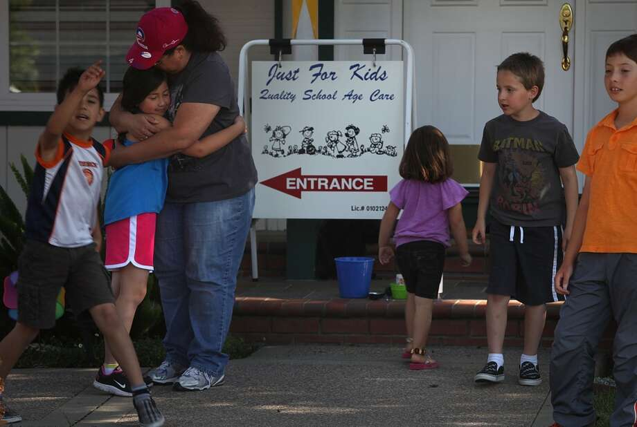 Linda Ross (left) hugs London Gibbs good bye as children leave her daycare center at her home in Livermore, Calif, near the end of the day on Wednesday, May 1, 2013.