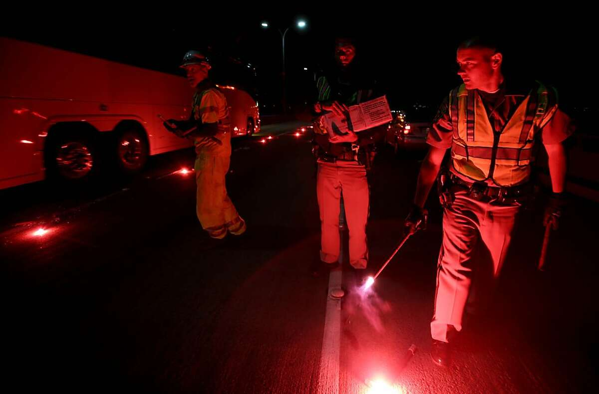 California Highway Patrolmen light flares as they investigate the scene of a limousine fire on the westbound side of the San Mateo-Hayward Bridge in Foster City, Calif., on Saturday, May 4, 2013. Five people died when they were trapped in the limo that caught fire as they were traveling, and four others and the driver were able to escape, according to the Oakland Tribune-Bay Area News Group. (AP Photo/Oakland Tribune-Bay Area News Group, Jane Tyska)