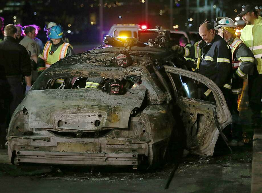 Workers investigate the scene of a limousine fire that killed five members of a bridal party on the San Mateo Bridge. Photo: Jane Tyska, Associated Press