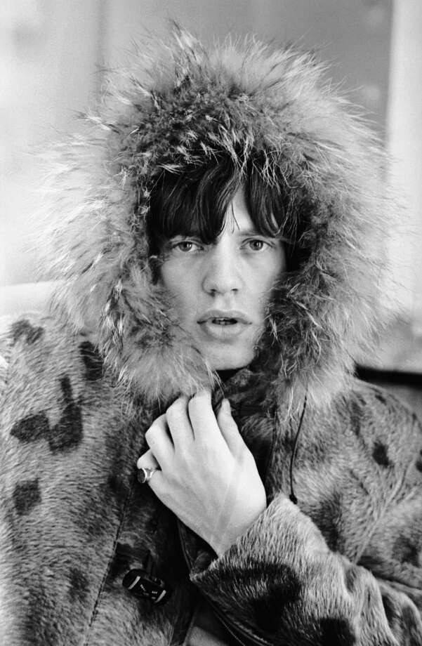 Rolling Stones singer Mick Jagger posing in a fur parka, with a fur trimmed hood, 1964. Photo: Terry O'Neill, Getty / 2006 Getty Images