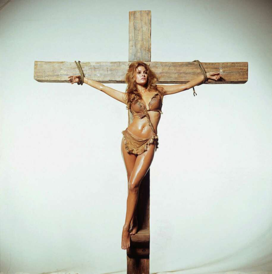 American actress Raquel Welch being crucified in an oddly anachronistic publicity still for the Hammer Films production 'One Million Years BC', directed by Don Chaffey, 1966. Photo: Terry O'Neill, Getty / 2005 Getty Images