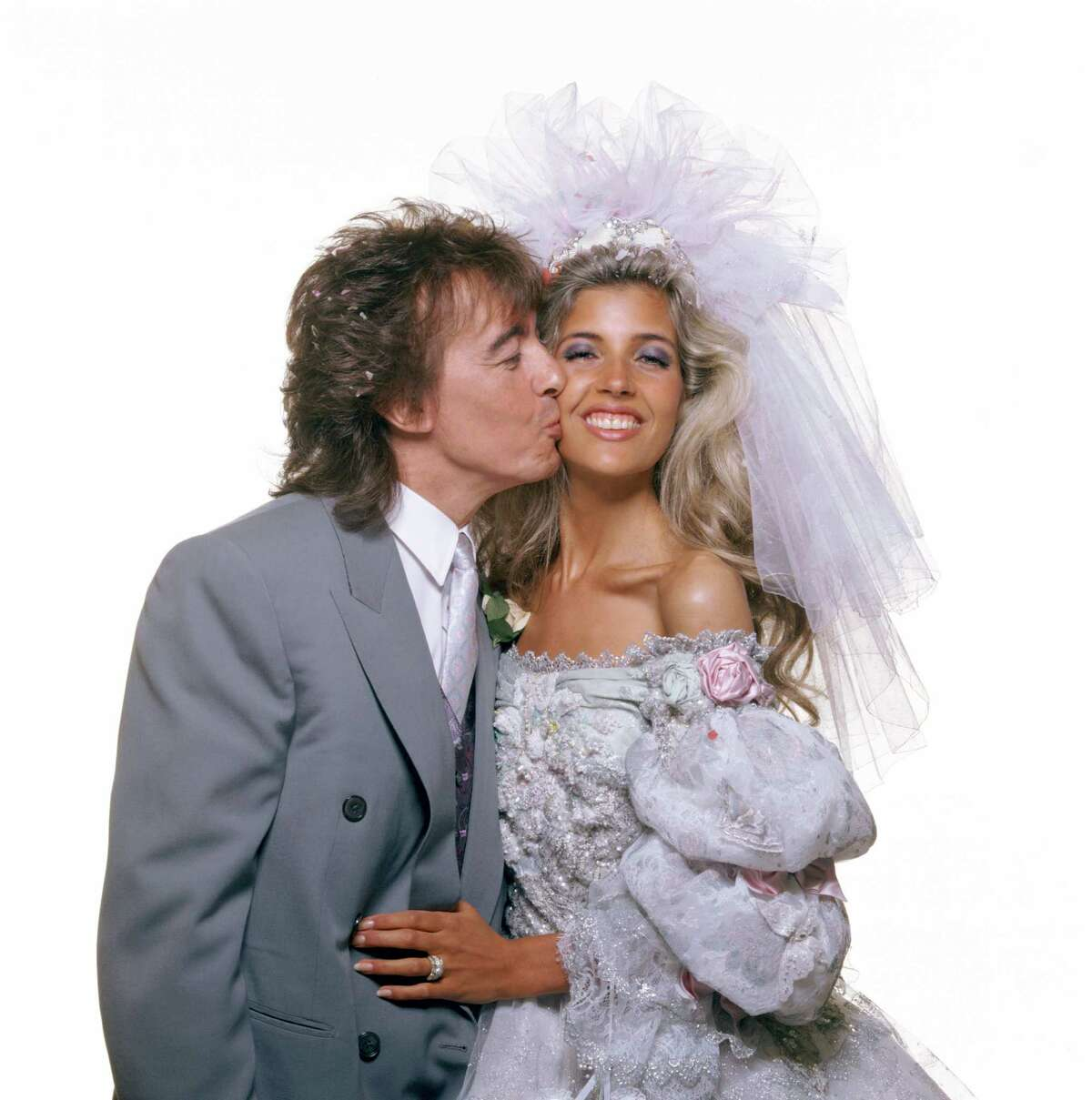 Rolling Stone bassist Bill Wyman kissing his new bride Mandy Smith on their wedding day in London, 5th June 1989.