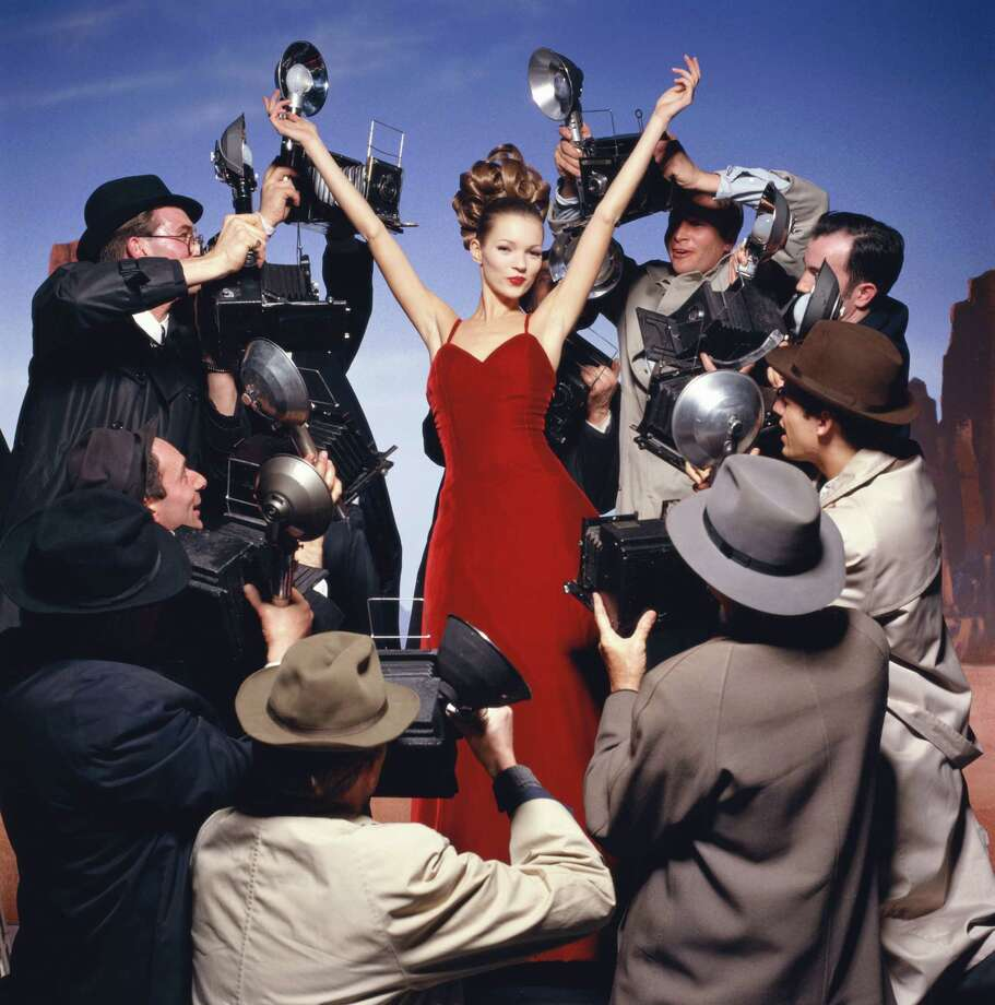 English model Kate Moss wearing a red velvet dress and surrounded by paparazzi photographers for a glamorous photo shoot, London 1993. Photo: Krause, Johansen, Getty / 2005 Getty Images