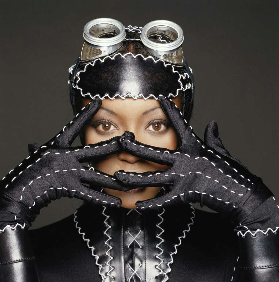 Model Naomi Campbell peeking through her fingers. She is wearing a stiched fetish style leather outfit and has goggles on her head, 1993. Photo: Terry O'Neill, Getty / 2005 Getty Images