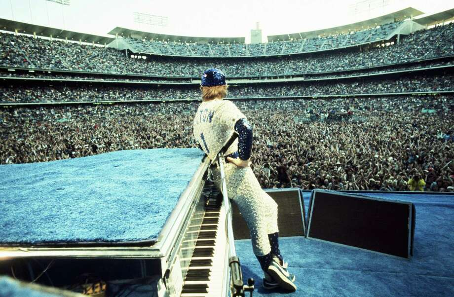 English singer songwriter Elton John performing at Dodger Stadium in Los Angeles, 1975. He is wearing a sequinned baseball outfit. Photo: Terry O'Neill, Getty / 2005 Getty Images