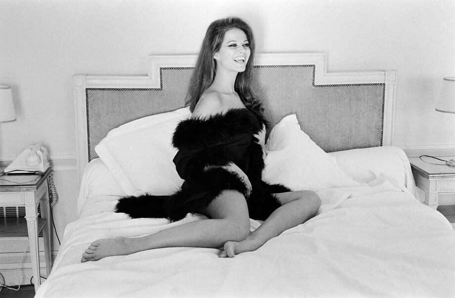 Italian actress Claudia Cardinale sitting on her bed in a fur trimmed robe. Photo: Terry O'Neill, Getty / 2005 Getty Images