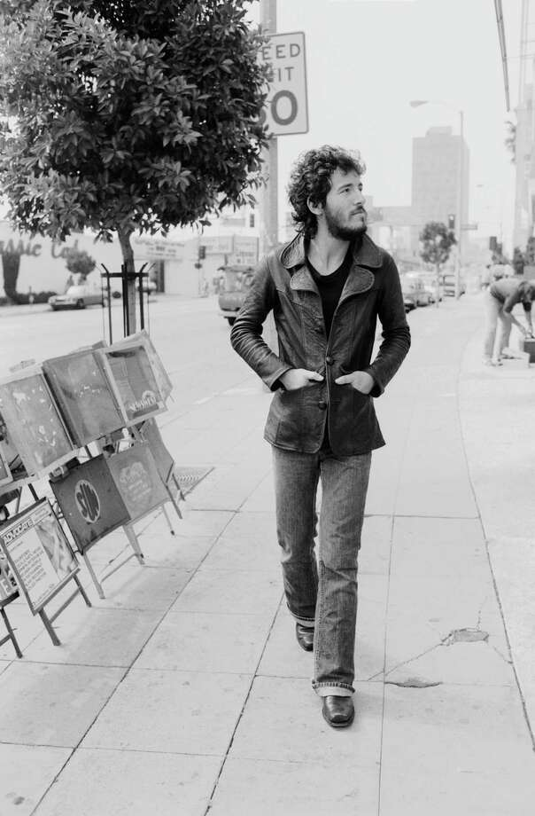 Singer Bruce Springsteen walking down Sunset Strip with his hands in the pockets of his leather jacket, 1975. He is in Los Angeles to promote his album Born To Run. Photo: Terry O'Neill, Getty / 2005 Getty Images