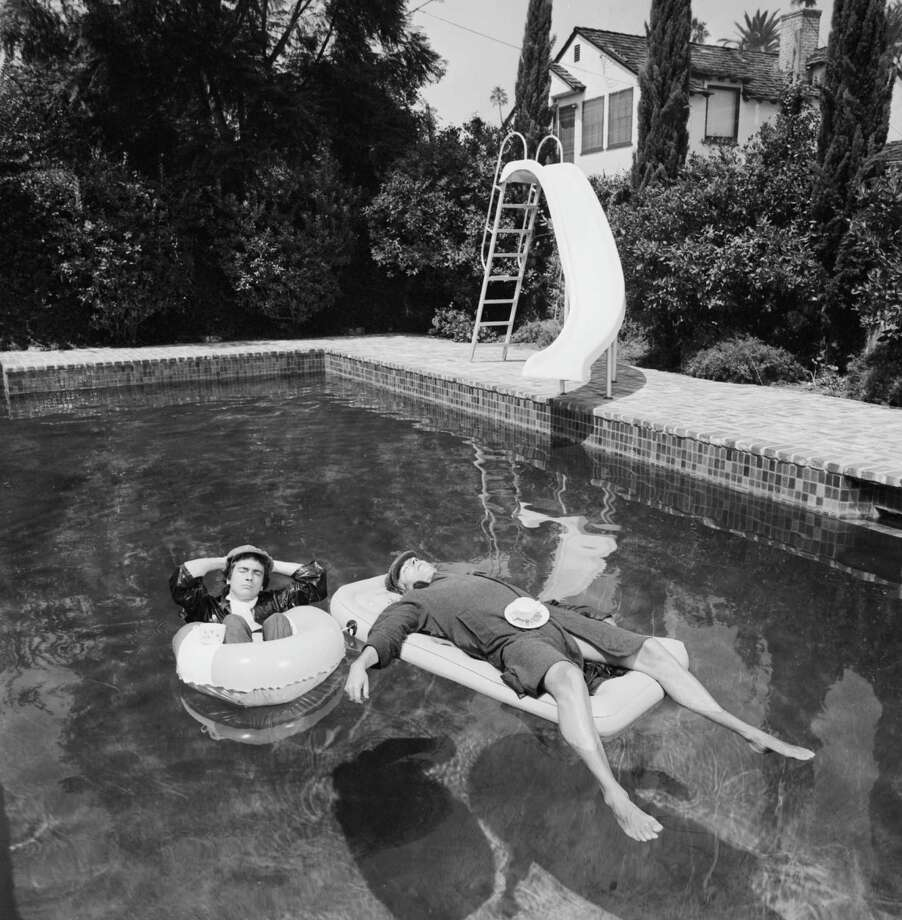 Comedians Peter Cook and Dudley Moore relaxing in a Beverly Hills swimming pool while in costume as the characters Pete and Dud, 1975. Photo: Terry O'Neill, Getty / 2005 Getty Images