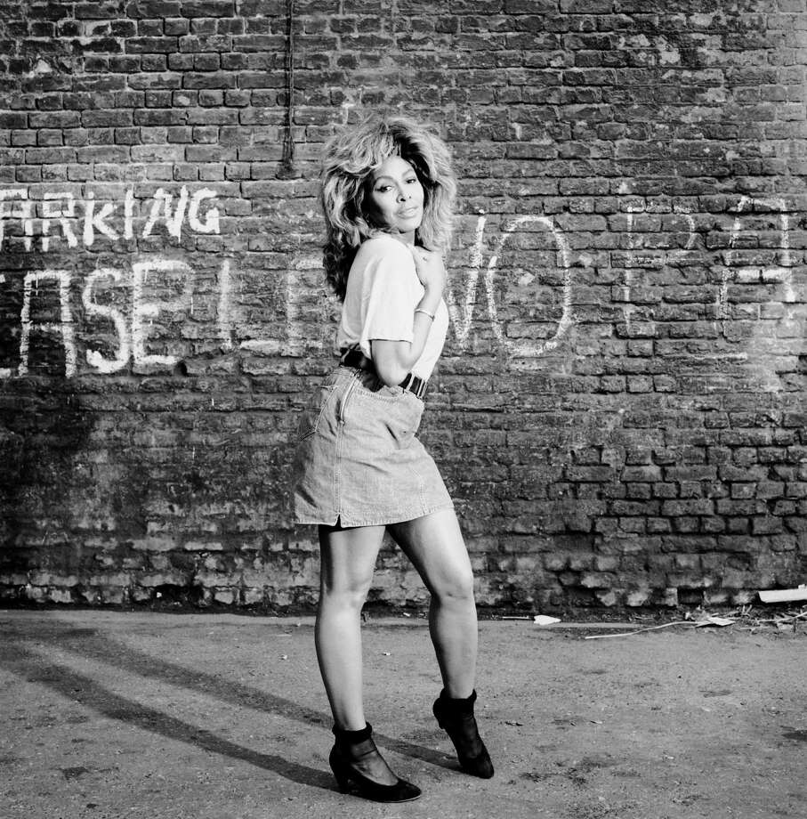 Singer Tina Turner posing in front of a brick wall with graffiti, London, 1993. Photo: Terry O'Neill, Getty / 2005 Getty Images