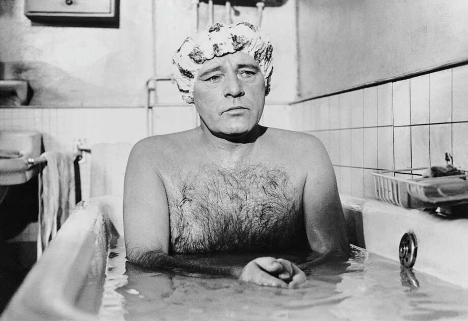 Welsh actor Richard Burton sitting in a bath looking thoughtful in a scene from Stanley Donen's 1969 film 'Staircase' in which he plays a hairdresser. He is wearing a shower cap. Photo: Terry O'Neill, Getty / 2005 Getty Images