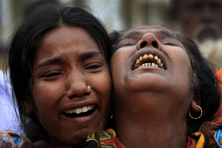 A woman is comforted as she grieves after identifying the body of her daughter, a victim of the garment factory collapse, Sunday, May 5, 2013 in Savar, near Dhaka, Bangladesh. The death toll from the collapse of a shoddily built garment-factory building in Bangladesh continued its horrifying climb, reaching 580 on Sunday with little sign of what the final number will be. The disaster is likely the worst garment-factory accident ever, and there have been few industrial accidents of any kind with a higher death toll. (AP Photo/Wong Maye-E) Photo: Wong Maye-E, Associated Press