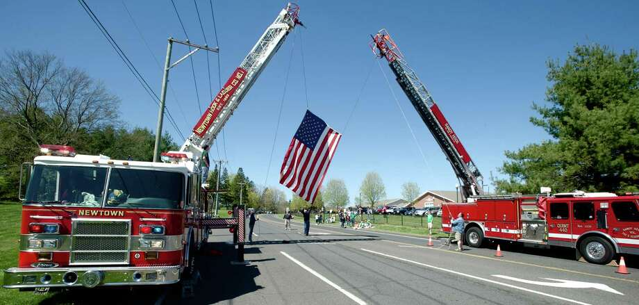 Fire fighter Rich Liska Jr, age 53, of Newtown Hook & Ladder holds the bottom of the flag as it's raised above Wasserman Way, in Newtown, Conn. It was part of  the route for the Green Ribbon Ride, on Sunday, May 5th, 2013. Photo: H John Voorhees III