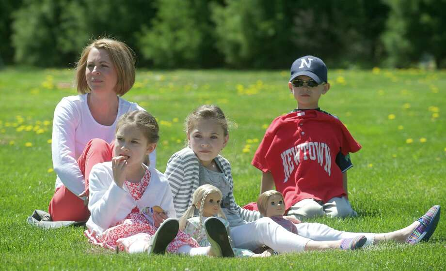 Sherri Patrick, age 41, watches the Green Ribbon Ride in Newtown, Conn, with her children, Olivia, age 8, Sadie, age 10, and Noah, age 7,  on Sunday, May 5th, 2013. Two of Noah's baseball teammates were victims of the Sandy Hook Elementary School shooting and he is displaying the teams jersey. Photo: H John Voorhees III