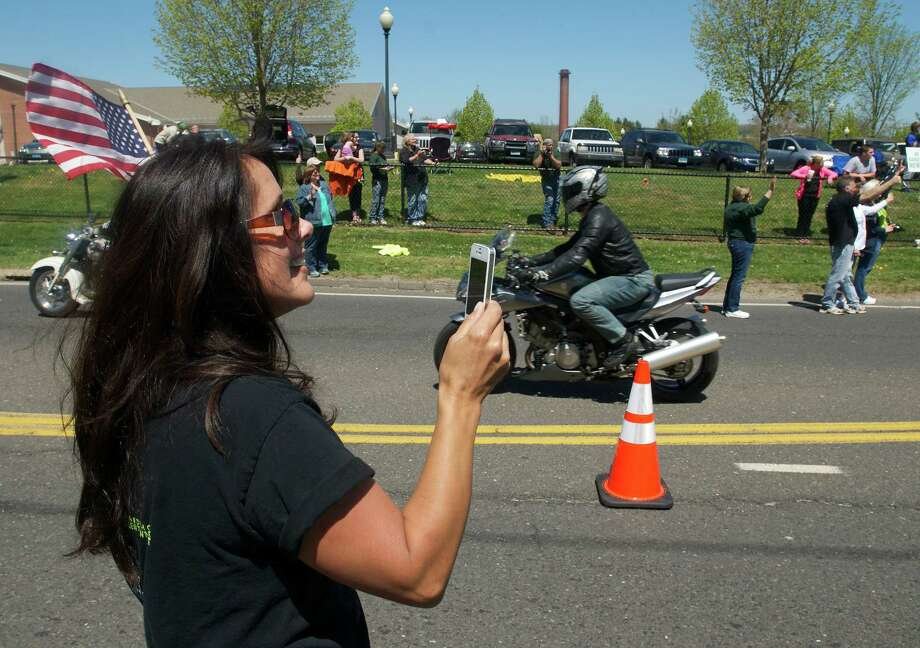 Joanne Amante, age 44, of Newtown,  videos riders in the Green Ribbon Ride as they pass through  Newtown, Conn on Sunday, May 5th, 2013. Photo: H John Voorhees III