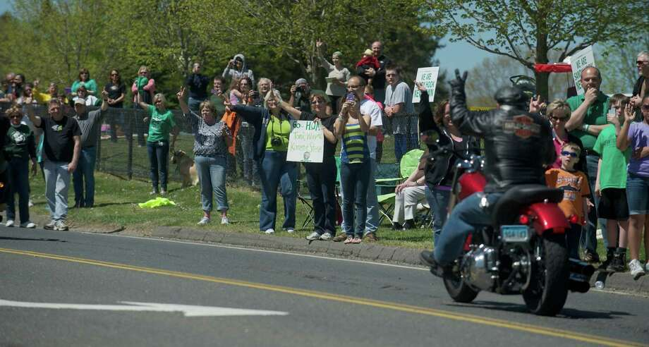 Spectators wave at a rider taking part in the Green Ribbon Ride as he passes through the town of Newtown, Conn, on Sunday, May 5th, 2013. Photo: H John Voorhees III