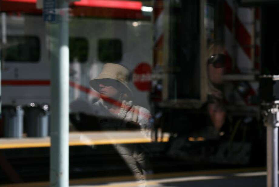 Passengers wait at the S.F. Caltrain station, reflected in a glass door. The trains are carrying so many riders in what is now a two-direction commute that they need to find a way to expand service. Photo: James Tensuan, The Chronicle