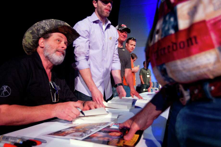NRA member and musician, Ted Nugent, greets fans and signs autographs at the National Rifle Association's 142 Annual Meetings and Exhibits in the George R. Brown Convention Center Sunday, May 5, 2013, in Houston.  The 2013 NRA Annual Meetings and Exhibits runs through Sunday, May 5.  More than 70,000 are expected to attend the event with more than 500 exhibitors represented. The convention will features training and education demos, the Antiques Guns and Gold Showcase, book signings, speakers including Glenn Beck, Ted Nugent and Sarah Palin as well as NRA Youth Day on Sunday Photo: Johnny Hanson, Houston Chronicle / © 2013  Houston Chronicle