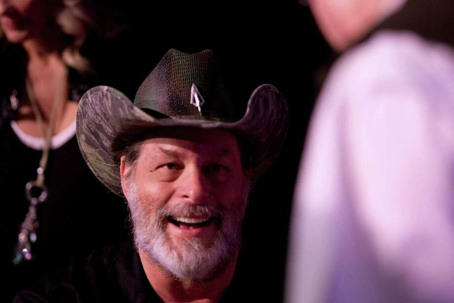 NRA member and musician, Ted Nugent, greets a fan while signing autographs at the National Rifle Association's 142 Annual Meetings and Exhibits in the George R. Brown Convention Center Sunday, May 5, 2013, in Houston.  The 2013 NRA Annual Meetings and Exhibits runs through Sunday, May 5.  More than 70,000 are expected to attend the event with more than 500 exhibitors represented. The convention will features training and education demos, the Antiques Guns and Gold Showcase, book signings, speakers including Glenn Beck, Ted Nugent and Sarah Palin as well as NRA Youth Day on Sunday Photo: Johnny Hanson, Houston Chronicle / © 2013  Houston Chronicle