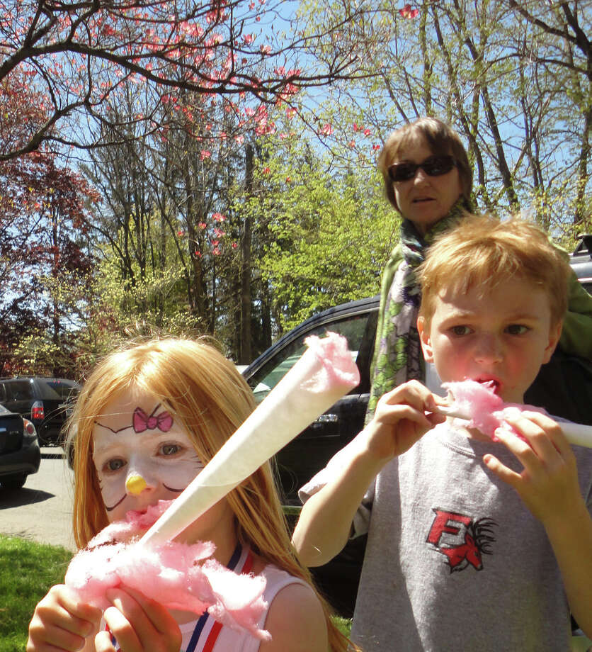 Kate Lochridge, 4, and brother Liam, 6, of Fairfield, enjoy pink cotton candy, harmonizing with pink dogwood blossoms, Saturday at the 78th Dogwood Festival. Photo: Meg Barone / Fairfield Citizen contributed