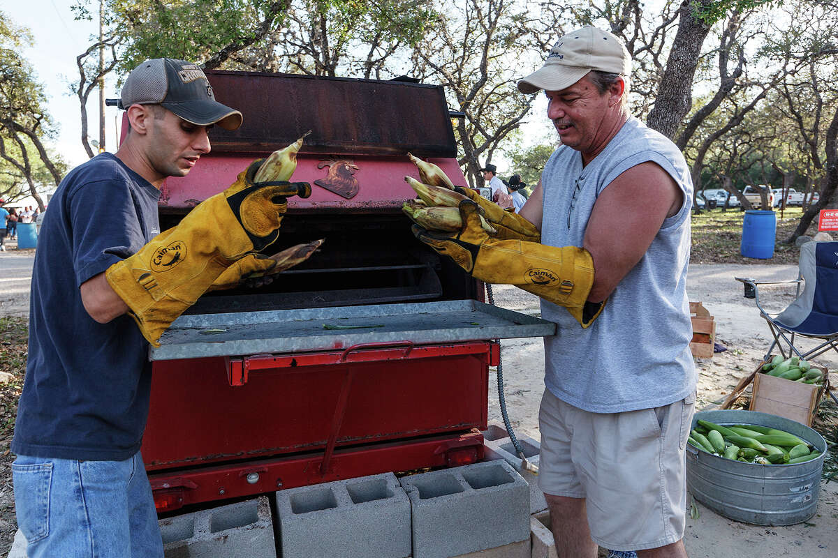Chip Chambers (right) and Joe pull roasted ears of corn from the roasting pit at the 47th annual Cornyval on the Helotes Festival Grounds on Saturday, May 4, 2013. Photo by Marvin Pfeiffer / Prime Time Newspapers